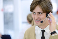 Smiling young call center executive at startup office Stock Photography