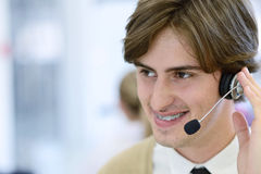 Smiling young call center executive at startup office Stock Images