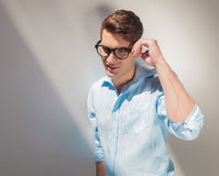 Smiling young casual man fixing his glasses Stock Images