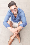 Smiling young casual man with glasses sitting on the sidewalk Stock Photography