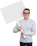 Smiling young casual man holding blank placard Royalty Free Stock Photo