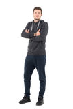 Smiling young casual man in sportswear with crossed hands looking at camera. Full body length portrait over white studio background Royalty Free Stock Photos