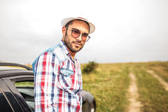 Smiling young casual man standing near a car Royalty Free Stock Photos