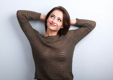 Smiling young casual woman in warm sweater looking up with hands Royalty Free Stock Photography