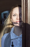 Smiling Young Caucasian Blond Woman Looking Out of the Doorway with Face Half Lit and Partially in Shadow Stock Photo