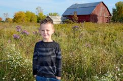 Smiling young Caucasian boy in rural field Stock Photography