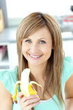 Smiling young caucasian woman holding a banana. Smiling young holding a banana looking at the camera in the kitchen at home Stock Image