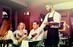 Smiling young cheerful waiter taking care of adults Royalty Free Stock Photo