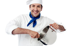 Smiling young chef holding vessel Royalty Free Stock Image