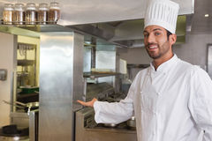 Smiling young chef looking at camera showing his workplace Stock Photography
