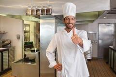 Smiling young chef looking at camera showing thumb up Royalty Free Stock Photo