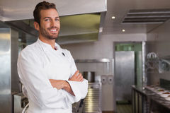 Smiling young chef standing with arms crossed. In a commercial kitchen royalty free stock photography