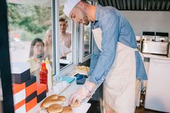 smiling young chef working in food truck while young people standing stock photo
