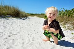 Smiling Young Child Playing in Sand at Beach Royalty Free Stock Photo