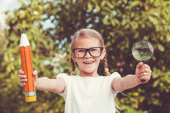 Smiling young child in a uniform standing against a tree in the Royalty Free Stock Photo