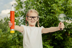 Smiling young child in a uniform standing against a tree in the Royalty Free Stock Images