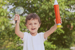 Smiling young child in a uniform standing against a tree in the Royalty Free Stock Photography