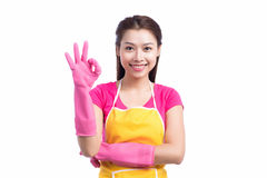 Smiling young cleaning asian lady with pink rubber gloves showing ok sign with thumbs up over white royalty free stock photo