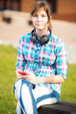 Smiling young college girl texting on a cell phone. Campus Royalty Free Stock Photo