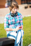 Smiling young college girl texting on a cell phone Royalty Free Stock Image