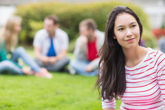 Smiling young college student with blurred friends in park Stock Photos