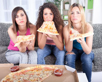 Smiling young companionship watching tv together and eath pizza Stock Photography