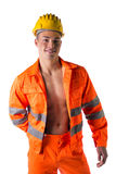 Smiling young construction worker with orange suit on naked torso. Handsome young construction worker with orange suit open on naked torso, smiling Stock Photo