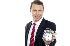 Smiling young consultant showing alarm clock Stock Photos