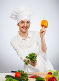 Smiling young cook holding parsley and yellow pepper Royalty Free Stock Photo