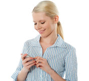 Smiling young corporate girl texting Stock Image