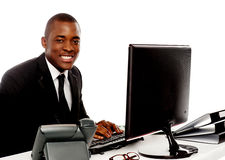 Smiling young corporate man using computer Royalty Free Stock Image