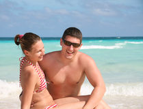 Smiling young couple against the ocean Stock Photo