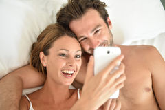 Smiling young couple in bed embracing and using smartphone Royalty Free Stock Image