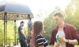 Smiling young couple with beer and looking at each other while two people barbecuing in the background. Smiling young couple with beer and looking at each other Stock Photography