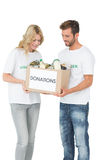 Smiling young couple carrying donation box Stock Image