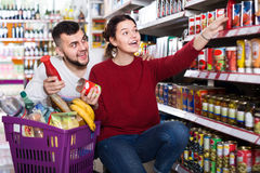 Smiling young couple choosing purchasing canned food for week at Royalty Free Stock Photos