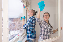 Smiling young couple cleaning windows Stock Image