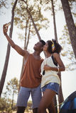 Smiling young couple clicking selfie while standing in forest Royalty Free Stock Images