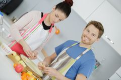 Smiling young couple cooking food in kitchen Stock Image