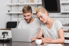 Smiling young couple with credit card using laptop. At home stock image