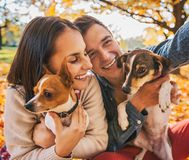 Smiling young couple with dogs outdoors in autumn park making se Royalty Free Stock Photography