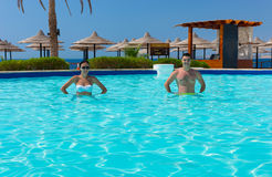Smiling young couple doing aqua fitness in swimming pool. At the hotel on a sunny summer day Royalty Free Stock Photos