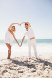 Smiling young couple doing heart shape Stock Photos