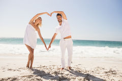 Smiling young couple doing heart shape Royalty Free Stock Image