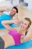 Smiling young couple doing sit ups at gym. Side view portrait of a smiling young couple doing sit ups at a gym Stock Photo