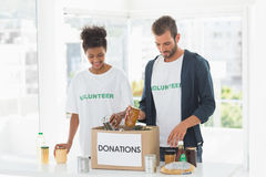 Smiling young couple with donation box Royalty Free Stock Images