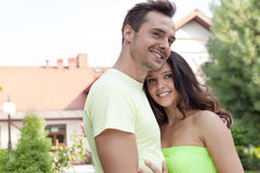 Smiling young couple embracing outdoors Stock Images