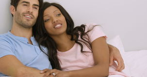 Smiling young couple embracing and talking on bed stock video footage