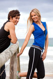 Smiling Young Couple By Fence at the Beach Stock Photography
