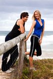 Smiling Young Couple By Fence at the Beach Stock Photo